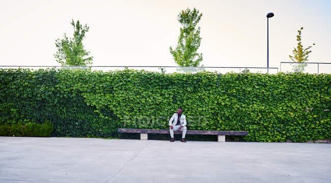 Hombre afroamericano sentado en un banco del parque. Es un hombre de negocios guapo.. - foto de stock