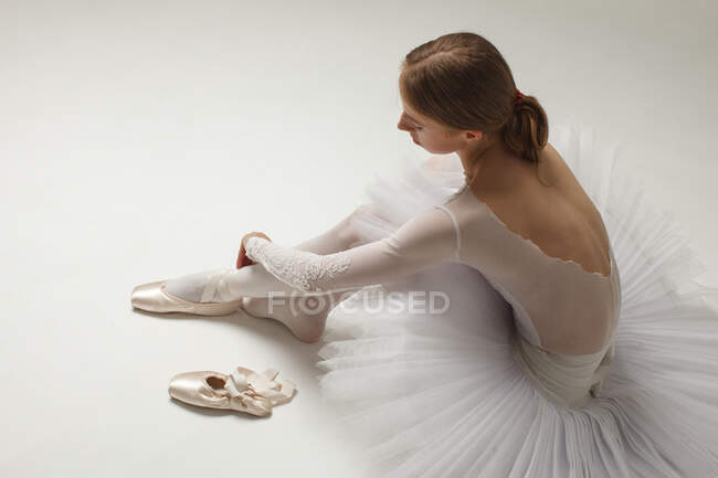 Young ballerina in white ballet dress Putting On Ballet Shoes, sitting on white floor — Stock Photo