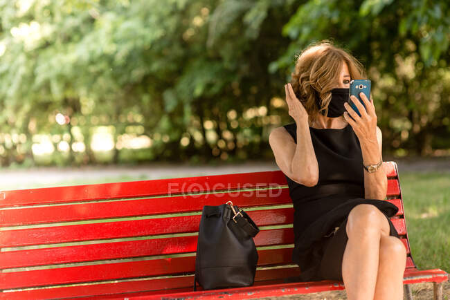 Portrait of an attractive elegant senior woman relaxing at the park between trees , fresh air, wearing an elegant black dress and face mask protection against coronavirus , a sunny summer day using a smartphone — стоковое фото