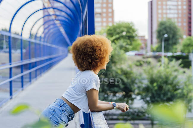 Woman with afro hair leaning on a bridge — Stock Photo