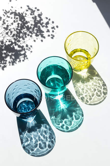 Colored glass cups filled with water with small flowers under the strong sunlight that enters through the window and casts colorful, textured shadows on a white table. Creative photography. — Stock Photo