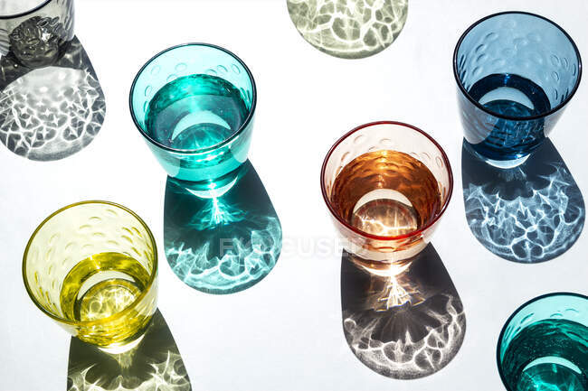 Set of coloured glass cups filled with water that shine under a strong light that projects its textured and coloured shadows on a white table. Creative photography. — Stock Photo