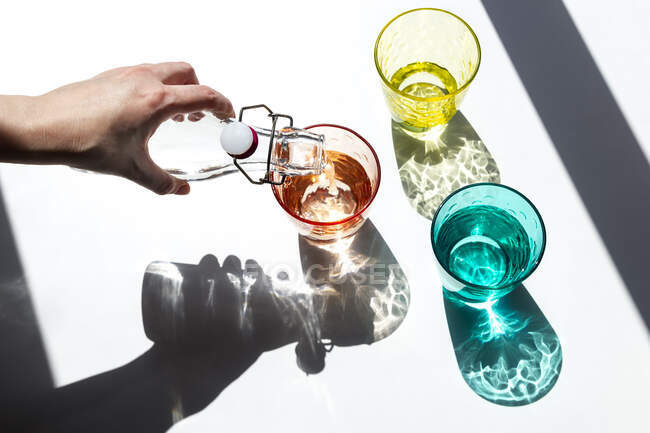 A person pours water into colored glass cups under the strong sunlight that enters through the window and casts its textured, colored shadows on a white table. Creative photography. — Stock Photo
