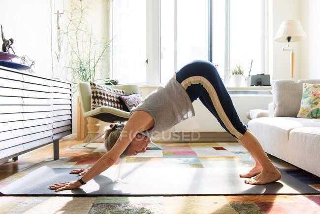Beautiful senior woman practicing yoga at home — Stock Photo