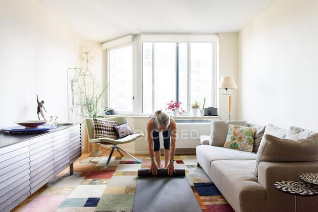 Старшая женщина с ковриком для йоги дома — стоковое фото