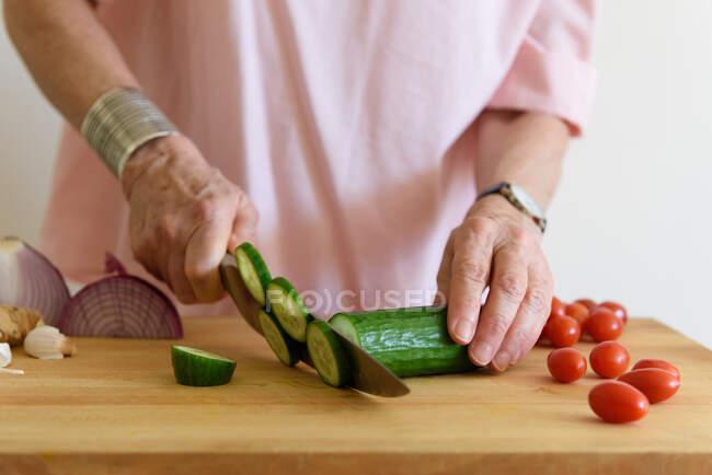 Senior woman making salad in kitchen — Stock Photo
