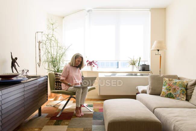 Senior woman using laptop computer at home — Stock Photo