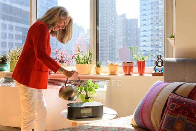 Donna anziana irrigazione piante a casa — Foto stock