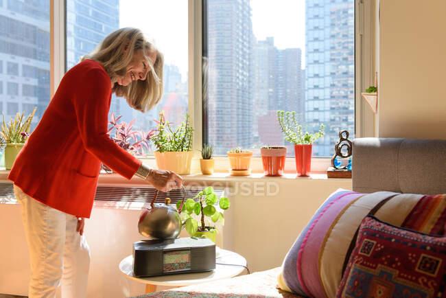 Старша жінка поливає квіти вдома. — стокове фото