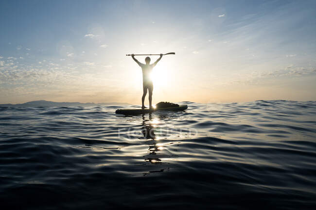 Konzept: Sieg und Glück. Mann auf einem Paddel-Surfbrett. Mitten im blauen Meer. Erhobene Arme halten das Ruder. Den Sonnenaufgang beobachten. Linsenschlag und Reflexionen. — Stockfoto