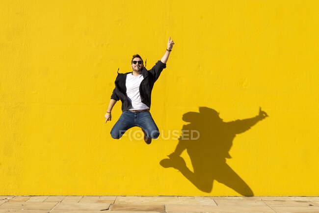 Jovem com óculos de sol pulando na frente de uma parede amarela. — Fotografia de Stock
