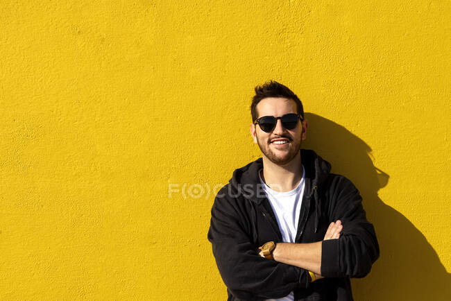 Junger bärtiger Mann steht mit verschränkten Armen vor einer gelben Wand — Stockfoto