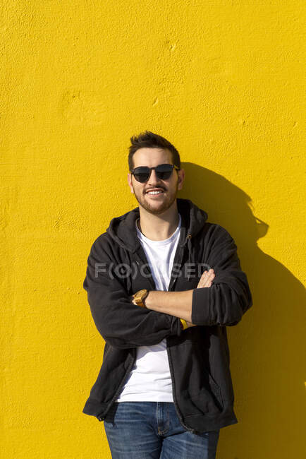 Young bearded man standing against a yellow wall with crossed arms — Stock Photo