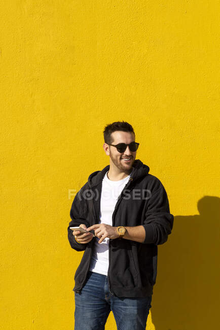 Bearded man with sunglasses standing against yellow wall, using phone — Stock Photo