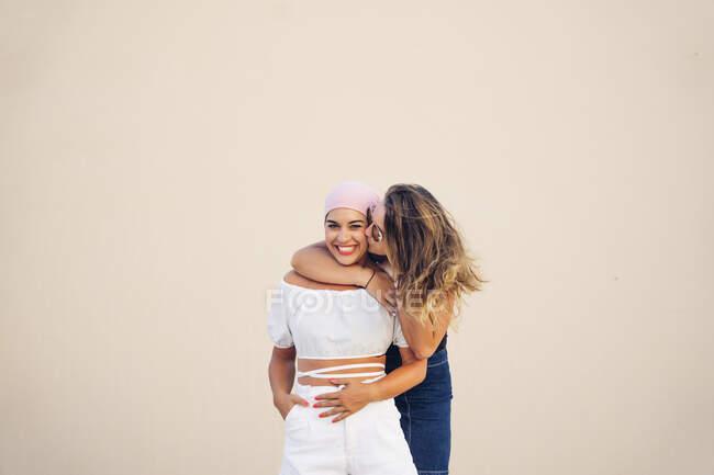 Jeune femme avec foulard rose lutte contre le cancer avec son ami. — Photo de stock