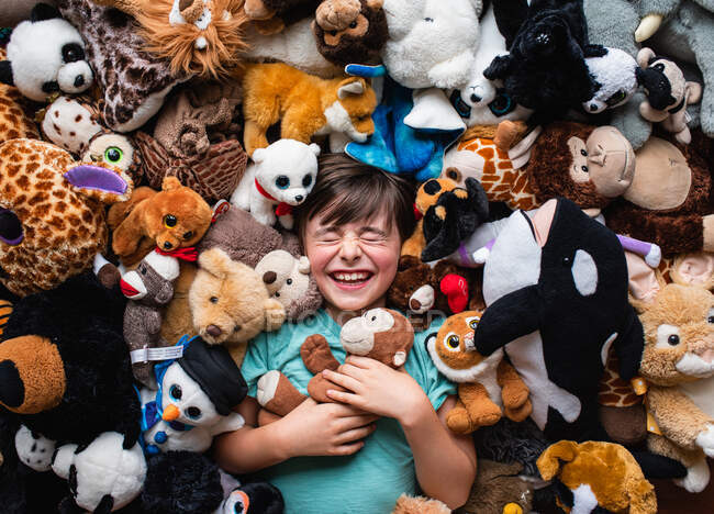 Happy young boy surrounded by his stuffed animals shot from above. — Stock Photo