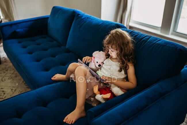 Cute little girl with tablet on sofa — Fotografia de Stock