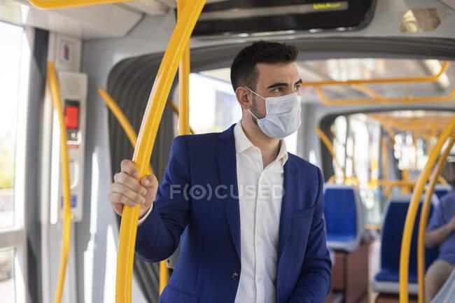 Geschäftsmann in der U-Bahn mit Maske gegen Coronavirus — Stockfoto