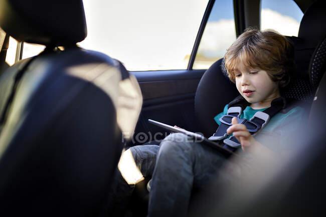 Симпатичный мальчик с планшетным компьютером во время поездки в машине — стоковое фото