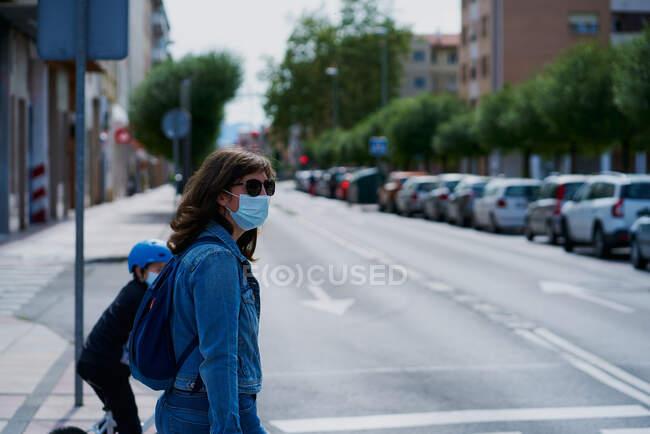 Mulher do outro lado da rua com uma máscara e óculos de sol — Fotografia de Stock