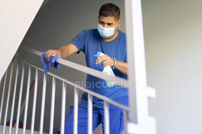 Уборщики дезинфицируют перила лестницы, чтобы избежать covid19 — стоковое фото