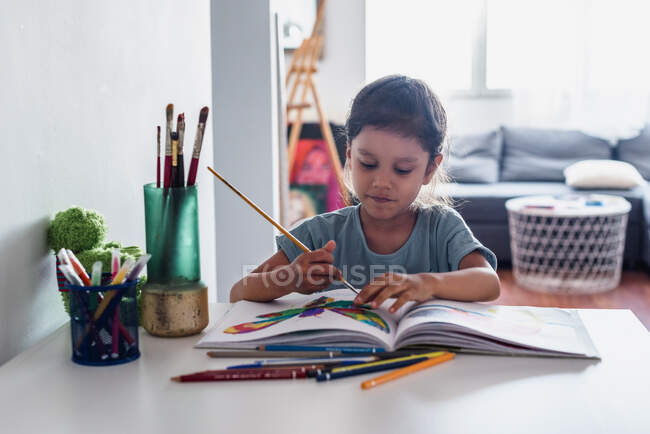 Hispanic girl painting on the desk with pencils and colors. — Stock Photo