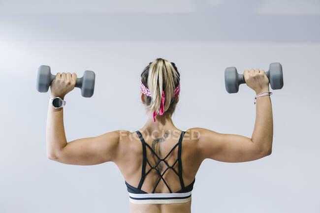 Vista posterior de la mujer rubia entrenando con pesas en el gimnasio - foto de stock