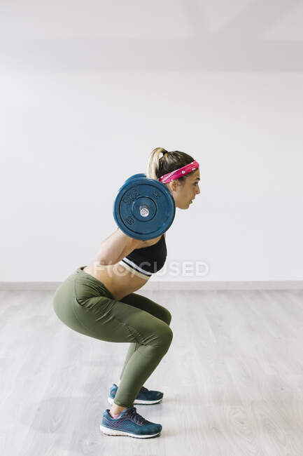 Side view of young woman working out with weights at gym — Stock Photo