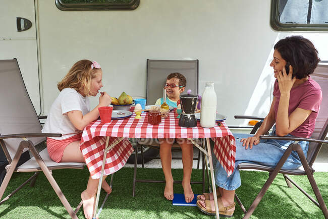 Mother having breakfast with her two children. They are enjoying their caravan vacation. — Stock Photo