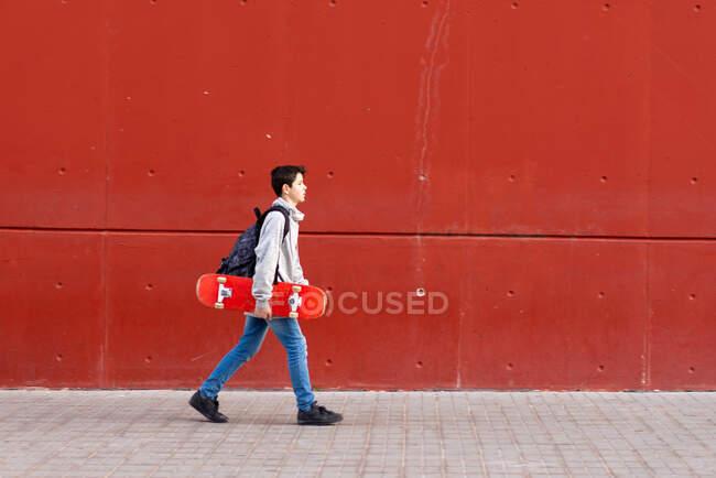 Niño sosteniendo un monopatín rojo mientras camina contra la pared roja - foto de stock