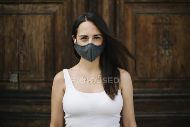 Primo piano della donna che indossa una maschera contro una porta — Foto stock