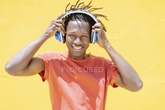 Felice uomo etnico indossando cuffie e ascoltando musica contro il muro giallo — Foto stock