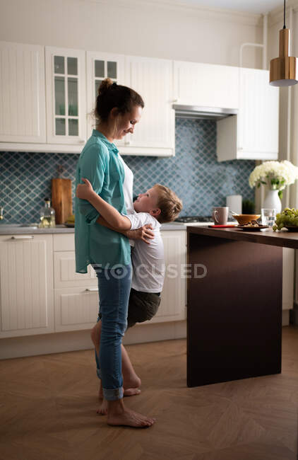 Full body adult woman playing with boy in cozy kitchen at home on weekend day — Stock Photo