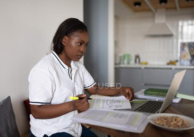 Этническая женщина с документами, считывающими данные с ноутбука во время учебы дома — стоковое фото