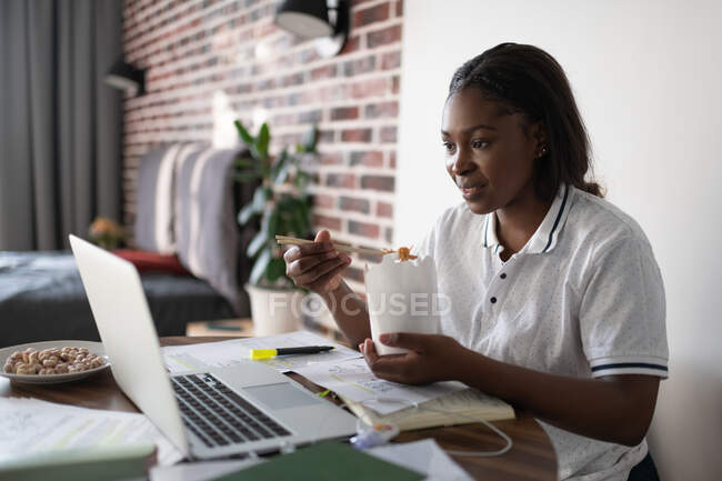 Черная женщина ест продукты питания и читает данные с ноутбука во время исследований — стоковое фото