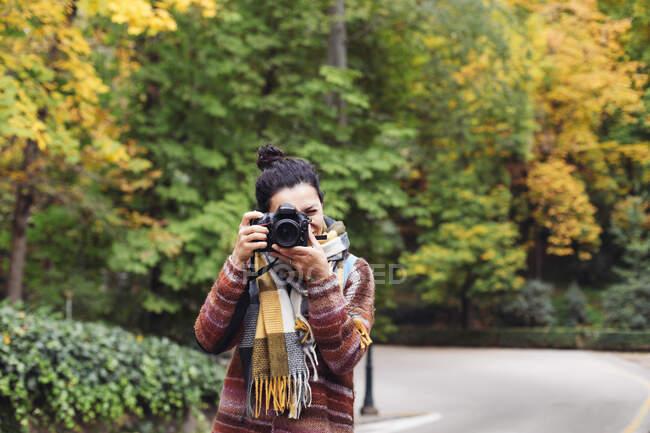 Ritratto di donna che scatta foto con macchina fotografica sullo sfondo della foresta autunnale — Foto stock