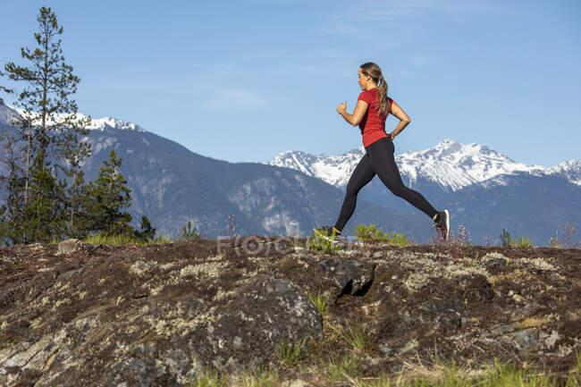 Женщина-атлет, бегущая возле гор — стоковое фото