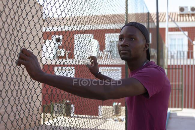 Молодий африкансько-мериканський чоловік тримає паркан на вулиці. — стокове фото