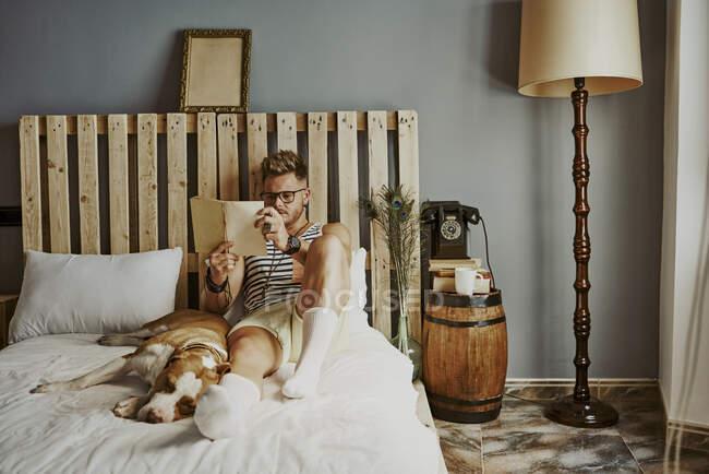Молодой блондин читает в постели со своей собакой. стиль жизни — стоковое фото