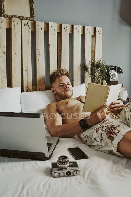 A man reads a book while working with his cell phone and laptop in a hotel bed. relax concept — Stock Photo