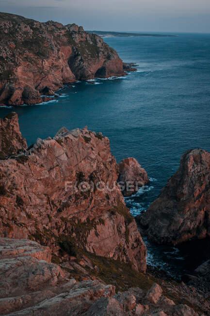 Bella vista di una scogliera nella baia del Mar Mediterraneo in lontananza, il sole tramonta di — Foto stock