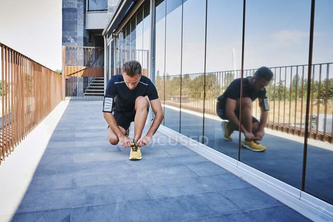 Спортсмен завязывает шнурки. На нём жёлтые кроссовки.. — стоковое фото