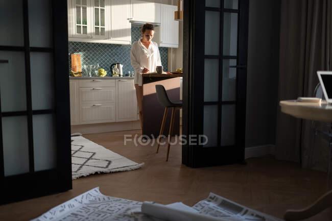 Eine erwachsene Frau steht in der Küche und arbeitet zu Hause an einem Architekturprojekt — Stockfoto