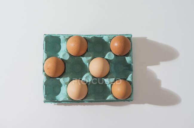Close-up view of raw chicken eggs in egg box on a white table — Stock Photo