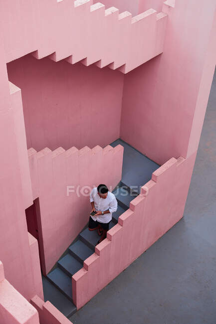 Young latin man goes down the stairs of a pink building — Stock Photo