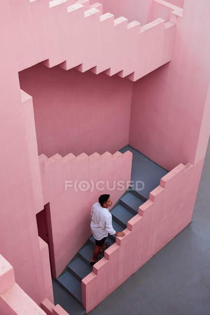 Giovane latino scende le scale di un edificio rosa — Foto stock