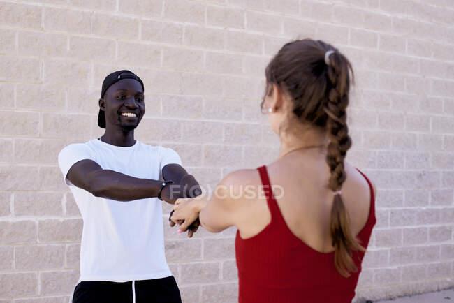 Interracial pareja juega y entrelaza sus brazos - foto de stock
