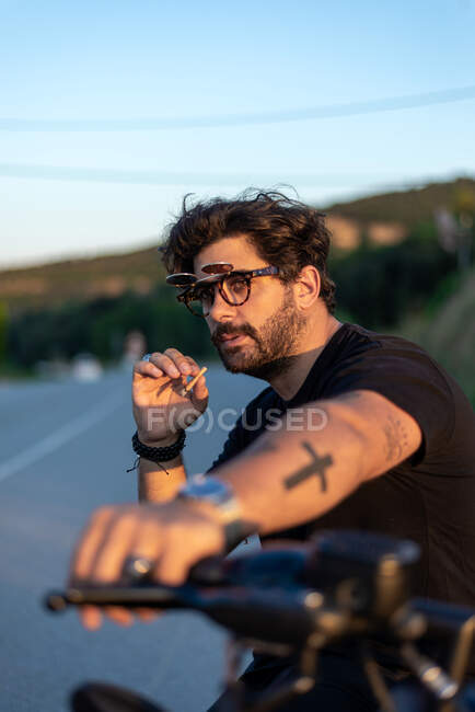 Fashionable young man sitting and smoking on a classic motorbike in sunset. — Stock Photo