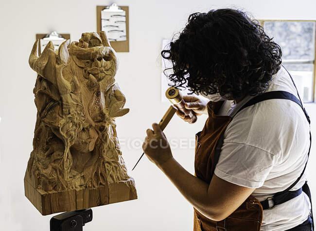 Escultor niña trabaja con un cuchillo y madera en el estudio - foto de stock