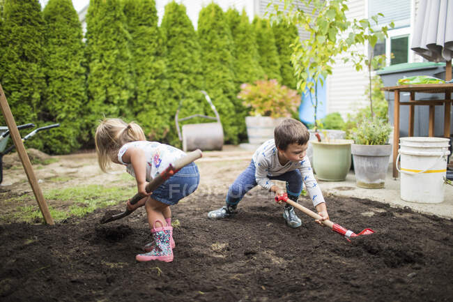 Kids helping parents with backyard project — Stock Photo